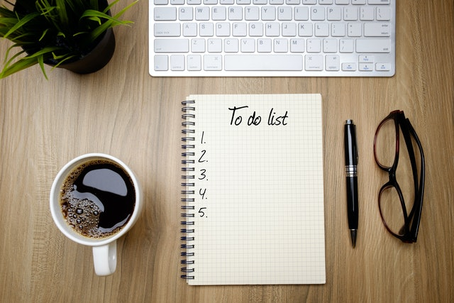 Book written To do list with coffee on wooden table