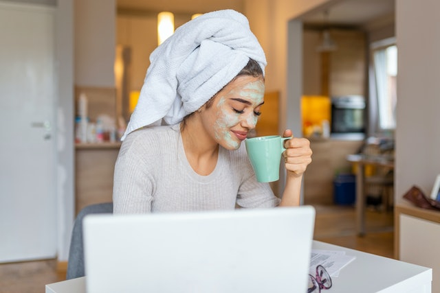 Beautiful girl with morning cosmetics mask drinking coffee - tea and reading newspaper. Summer morning routine. Portrait of a woman with beauty mask on her face