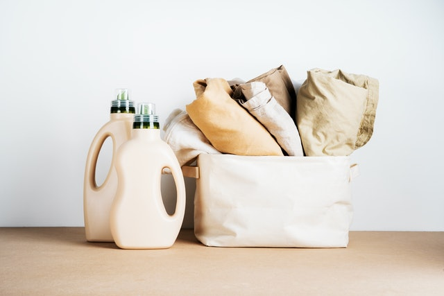 Eco Design of natural blank bottles packaging of detergent for laundry with basket of clean cotton things on table. Space for text. Bio organic product.