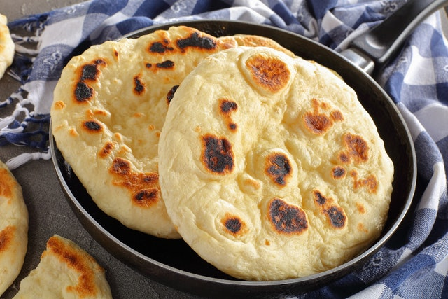 freshly pan fried pita bread in skillet with kitchen towel on concrete table, view from above, close-up