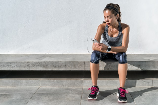 Fitness runner on mobile smart phone app tracking progress listening to music with earphones for fitness motivation. Athlete runner in sportswear relaxing sitting getting inspired. Asian mixed race.