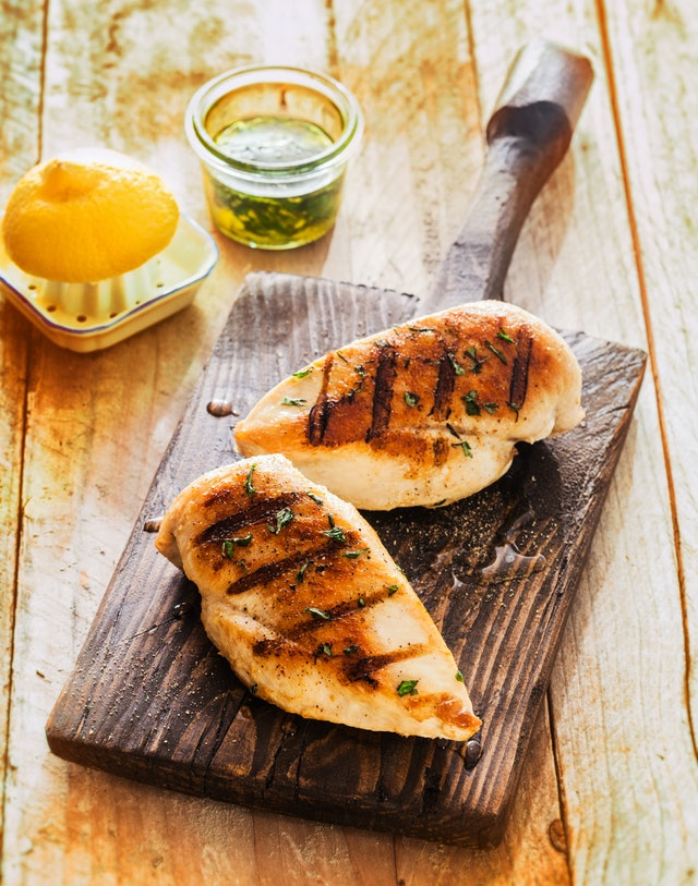 Healthy grilled chicken breasts marinated with lemon and olive oil and cooked on a summer BBQ served on an old wooden board