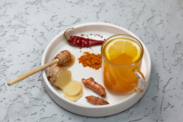 morning detox drink turmeric in the glass on a gray concrete background. copy space