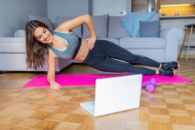 Young woman exercising at home in a living room. Video lesson. Young woman repeating exercises while watching online workout session. Beautiful young woman doing fitness exercise at home