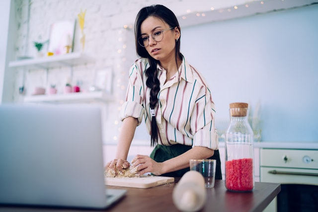 Charming black haired woman in striped shirt and glasses kneading dough while watching food recipe tutorial at laptop in modern kitchen