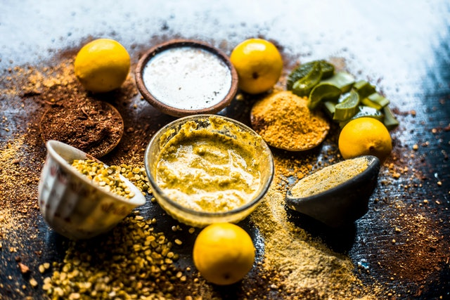 Ayurvedic face pack or ubtan of moong dal or green lentil or mung dal with lemon,dried orange peel powder,chandan powder or sandal wood powder,milk and aloe vera gel on wooden surface.