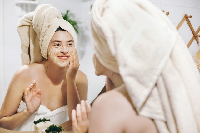 Skin Care concept. Young happy woman in towel making facial massage with organic face scrub and looking at mirror in stylish bathroom. Girl applying scrub cream, peeling and cleaning skin