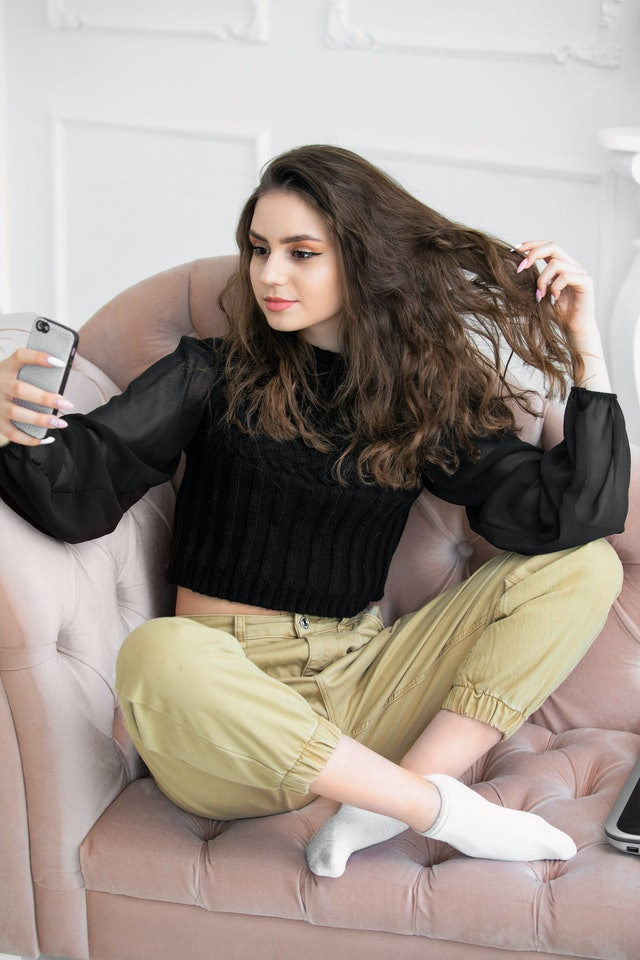 girl sitting on a sofa in a beautiful setting takes a selfie on a telephon