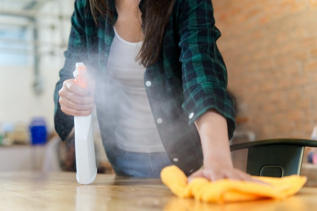 Close up view of woman cleaning a house. She is wiping dust using a spray and a orange fabric while cleaning on the table. Focus on the foggy. Happy house cleaning concept.