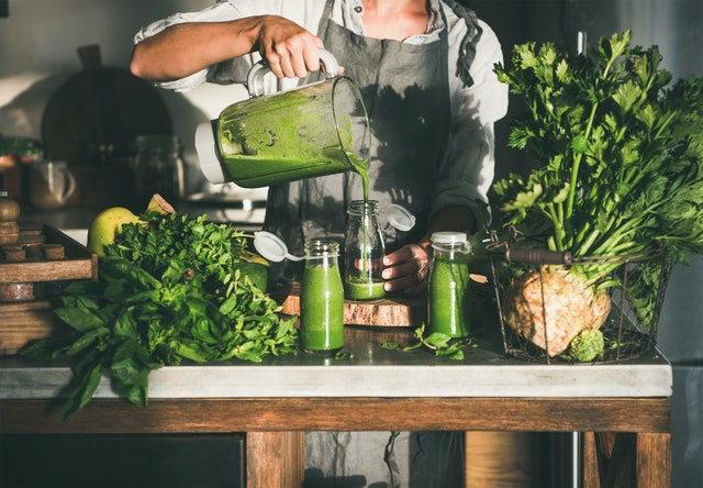 Making green detox take-away smoothie. Woman in linen apron pouring green smoothie drink from blender to bottle surrounded with vegetables and greens. Healthy, weight loss food concept