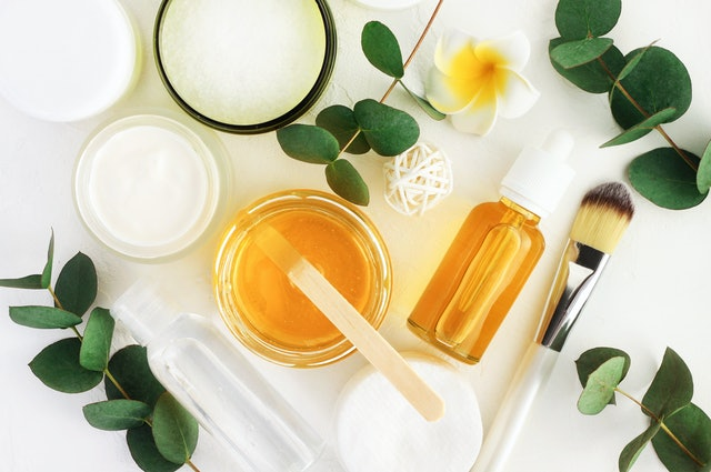 Natural cosmetics ingredients for skincare, body and hair care. Golden honey in jar and green herbal eucalyptus leaves. Top view bottles with facial treatment product white background
