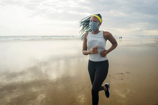 A person wearing a yellow headband and white tank top runs on the beach while wearing a mask. Going out for a socially-distant, masked run is relatively safe during quarantine.